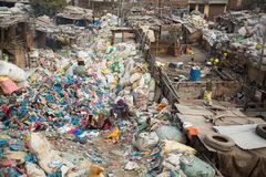Unidentified people from poorer areas working in sorting of plastic on the dump. Royalty Free Stock Photo