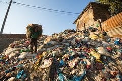 Unidentified people from poorer areas working in sorting of plastic on the dump. Stock Photo