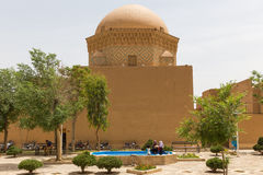 Unidentified people resting in an ancient square in the old town of Yazd stock image