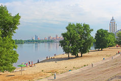 Unidentified people are resting on the beach of Dnipr river in Obolon district Stock Image