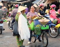 Unidentified people are selling foods and fruits on the street in the wet market, Mekong delta area, Vietnam. Stock Photo