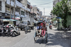 Unidentified people on a street in Surabaya. SURABAYA, INDONESIA - OCT 21, 2015 : Unidentified people on a street in Surabaya. Rickshaw is the cheapest Stock Photography