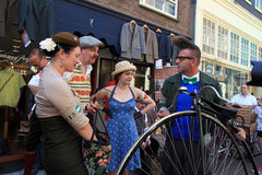 Unidentified people in vintage style clothes with their bicycles Stock Photo