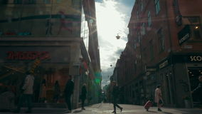 Unidentified People Walk Along A Busy Street. STOCKHOLM, SWEDEN - APRIL 22, 2015: Slow motion clip of a unidentified people walk along a busy street over sun stock video footage