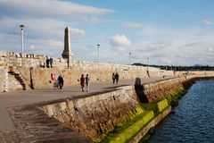 Unidentified people walk along Dun Laoghaire's East pier, Ireland. Royalty Free Stock Image