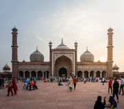 Unidentified people walk in courtyard of Jama Masjid at sunset in Delhi,India. The Masjid-i Jahān-Numā, commonly known as the Jama Masjid of Delhi, is the Royalty Free Stock Photo