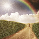 Unidentified people walking through the fields itry road w. Unidentified people walking through the fields in country road with white cloud, sunbeam and rainbow Stock Photo