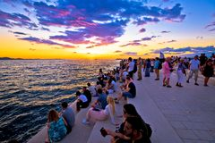 Unidentified people on Zadar sea organs. ZADAR, CROATIA - July 18 2017: Unidentified people on Zadar sea organs at sunset. Many tourists visits unique stock photography