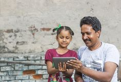 A girl studying elementary education in open school. Unidentified person in ludhiana, punjab, india helping his unidentified daughter in study through digital Stock Photos