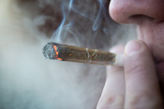 Unidentified person smoking marijuana joint drug closeup Stock Photo