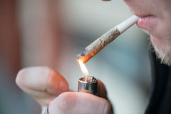 Unidentified person smoking marijuana joint drug closeup Stock Photos