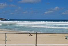 Unidentified person in a sunbed enjoying view of the waves on empty Bondi Beach in Sydney. Australia Royalty Free Stock Image