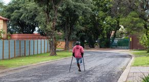 Unidentified physically disabled man on crutches. Johannesburg, South Africa - unidentified physically disabled man struggles on his crutches through a street in Royalty Free Stock Photos
