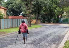 Unidentified physically disabled man on crutches. Johannesburg, South Africa - unidentified physically disabled man struggles on his crutches through a street in Stock Photography