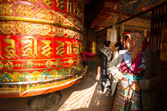 Unidentified pilgrimage near spinning Big Tibetan Buddhist prayer wheel at Boudhanath Stupa, Dec 20, 2013 in Kathmandu, Nepal. Stock Photos