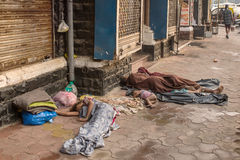Unidentified poor people sleep at the street in Mumbai, India. stock image
