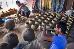Unidentified potter making clay water pots on pottery wheel. royalty free stock photography