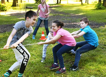 Unidentified preteen kids play rope pull game Stock Photo