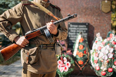 Unidentified reconstructor dressed as Soviet. Soldier with submachine gun, standing on background of mass grave of Soviet soldiers who died during battles for Royalty Free Stock Images