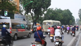 Unidentified riders ride motorbikes on busy road stock video