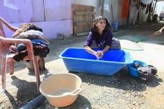 Unidentified Roma woman wash clothes  Stock Photos
