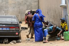 Unidentified Senegalese group of people gather near the car. LAC ROSE reg. , SENEGAL - APR 27, 2017: Unidentified Senegalese group of people gather near the car stock images