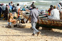 Unidentified Senegalese people gather near the boats on the coa. KAYAR, SENEGAL - APR 27, 2017: Unidentified Senegalese people gather near the boats on the coast stock photos