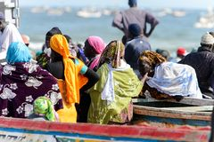 Unidentified Senegalese people gather near the boats on the coa. KAYAR, SENEGAL - APR 27, 2017: Unidentified Senegalese people gather near the boats on the coast royalty free stock photos