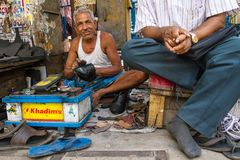 Unidentified shoe shiner does his job at street of Kolkata Stock Images