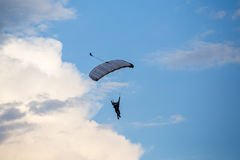Unidentified skydiver, parachutist on blue sky Stock Photos
