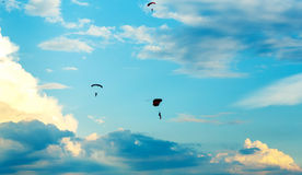 Unidentified skydivers, parachutist on blue sky Royalty Free Stock Photos