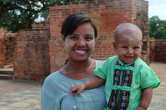 Unidentified smilling mother and son with thanakha on their faces in Myanmar. Stock Images