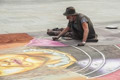Unidentified Street artist drawing on the pavement with chalk and create an original chalk art piece Royalty Free Stock Photos