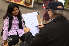 Unidentified street artist drawing a picture Royalty Free Stock Image