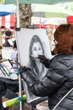 Unidentified street artist on Montmartre. Unidentified street artist drawing a portrait at Place du Tertre on Montmartre, Paris. The area once attracted famous Royalty Free Stock Photo