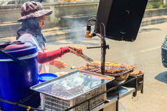 Unidentified street food vendor grilling chicken on smoky oven. Royalty Free Stock Photography