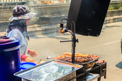 Unidentified street food vendor grilling chicken on smoky oven. Stock Photography