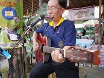 Unidentified street musician plays guitar at walking street market. SAMUTPRAKRAN, THAILAND - FEBRUARY 11 :Unidentified street musician plays guitar at walking Stock Images