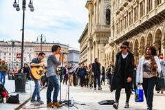 Unidentified street performers at Duomo di Milano. MILAN, ITALY - 14 APRIL 2018 - Unidentified street performers play guitar and sing the song in public area stock photos