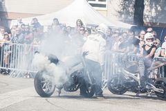 Unidentified stunt rider makes slide slinding on the road. With lot of smoke royalty free stock photos