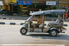 Unidentified taxi driver with traditional tuk-tuk in Thailand. Royalty Free Stock Image
