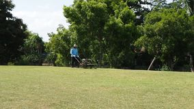 An unidentified Thai man mows the lawn. NONTHABURI, THAILAND - MAY 26, 2015: an unidentified man mows the lawn at Chaloem Kanchanaphisek Park on May 26, 2015 in stock footage