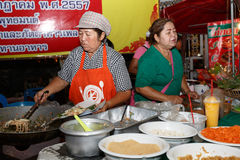 An unidentified Thai people sells pad thai on night market wall street. Stock Images