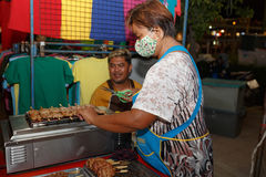 An unidentified Thai people sells roasted pork on night market walk street. Stock Photography