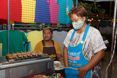 An unidentified Thai people sells roasted pork on night market walk street. Royalty Free Stock Image