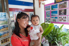 An unidentified Thai woman with cute baby at work in travel agent office in Phang Nga province Royalty Free Stock Photography