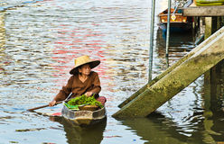 An unidentified Thai woman sells her goods in her boat Stock Photo