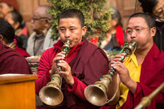 Unidentified tibetan Buddhist monks near stupa Boudhanath during festive Puja Stock Photo