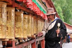 Unidentified Tibetan pilgrims turn the prayer wheels royalty free stock photos
