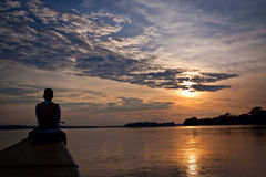 Unidentified tourist in a canoe contemplating. ORELLANA, ECUADOR - AUGUST 13, 2012: Unidentified tourist in a canoe contemplating stunning rainforest sunset royalty free stock images